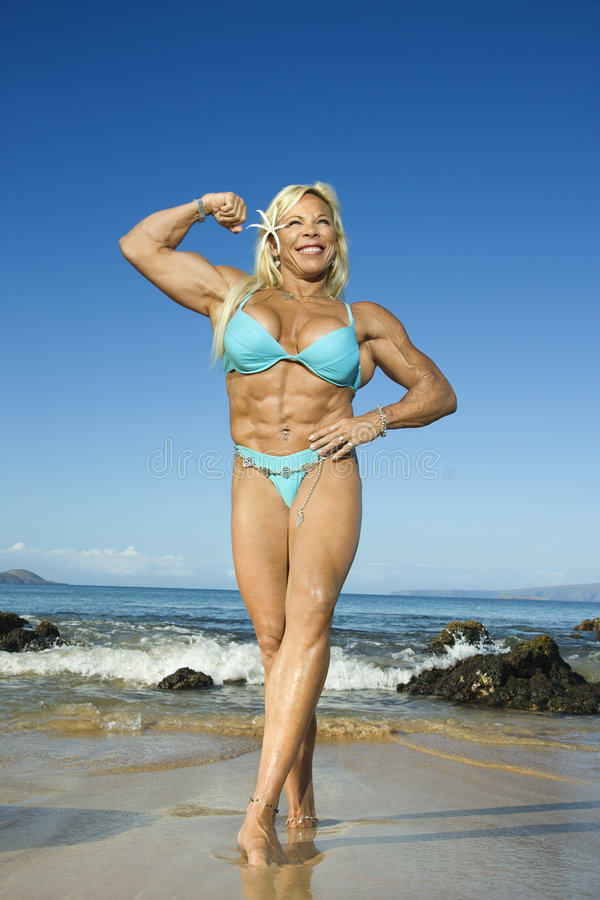 Bodybuilder da mulher na praia. foto de stock