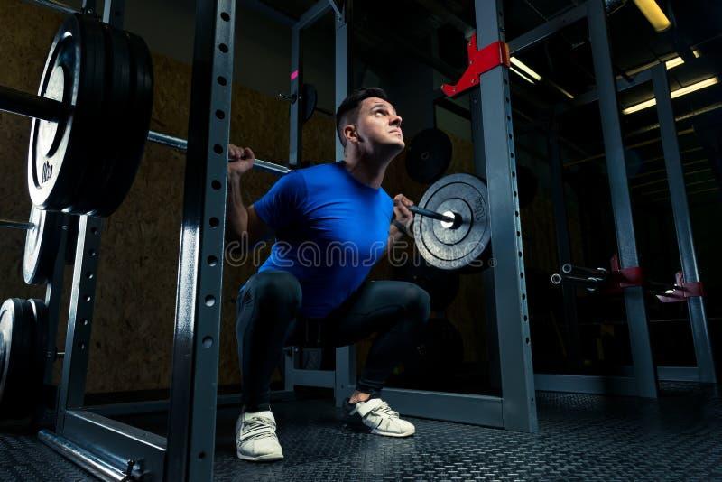 bodybuilder dans un T-shirt bleu avec un barbell dans le gymnase photographie stock libre de droits
