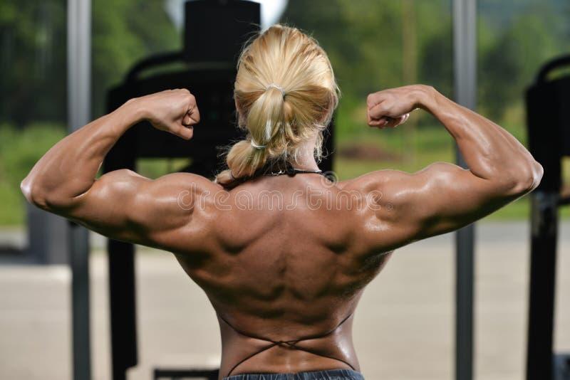 Bodybuilder de femme fléchissant des muscles photographie stock
