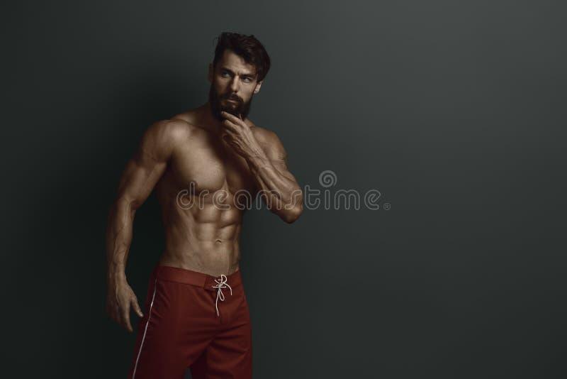 Bodybuilder in den roten kurzen Hosen auf Wandhintergrund stockfotografie
