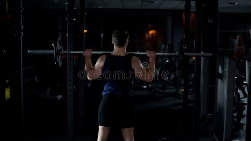 Bodybuilder, der Übung mit Barbell, den Trainingsarmen und den Schultermuskeln tut lizenzfreies stockbild