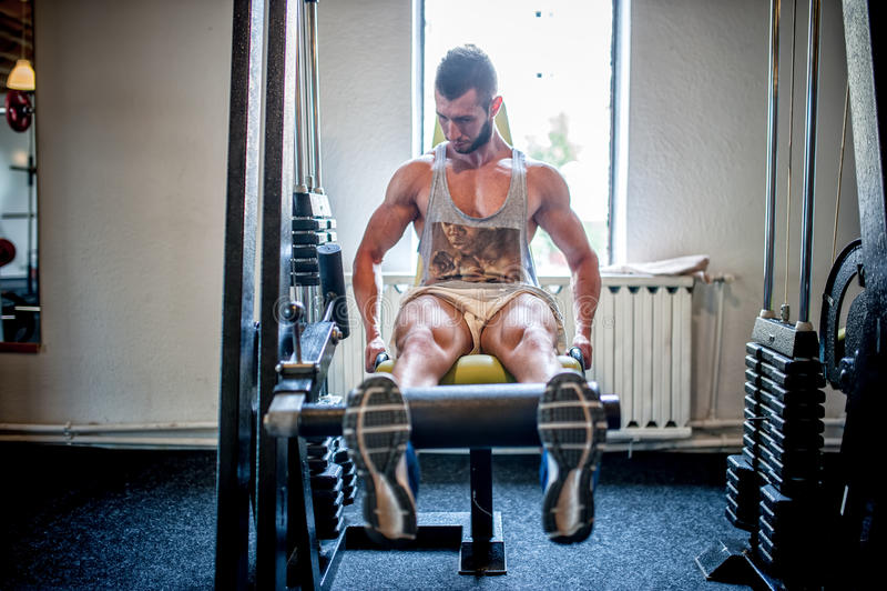 Bodybuilder, der an der Turnhalle, an den Beinen und an den Füßen ausarbeitet und ausbildet stockfoto