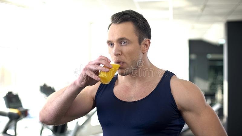 Bodybuilder, der frischen Orangensaft, ausgeglichene Eignungsnahrung, Training trinkt stockbilder