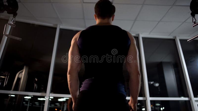 Bodybuilder, der nach Kastenmuskeltraining auf Kabelmaschine an der Turnhalle sich entspannt lizenzfreies stockbild