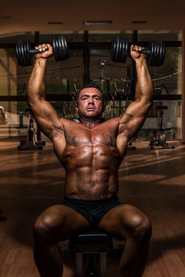 Bodybuilder, der Schulterpresse Whitdummkopf tut lizenzfreies stockbild