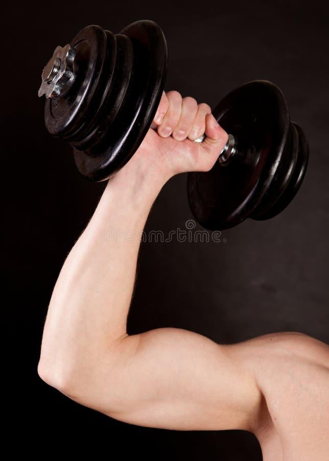 Bodybuilder, der sein bicep ausbildet lizenzfreies stockfoto