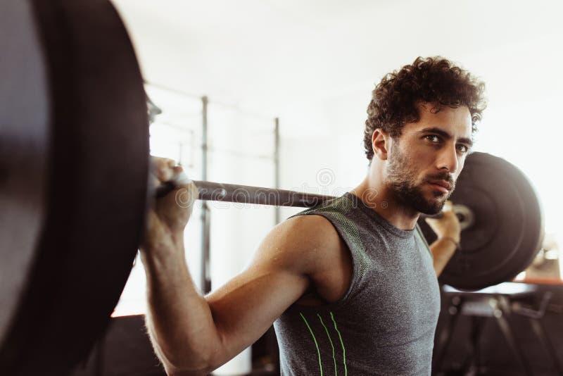 Bodybuilder, der an der Turnhalle mit schweren Gewichten ausarbeitet stockbilder