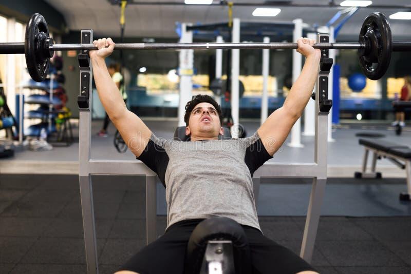 Bodybuilder des jungen Mannes, der Gewichtheben in der Turnhalle tut lizenzfreie stockbilder