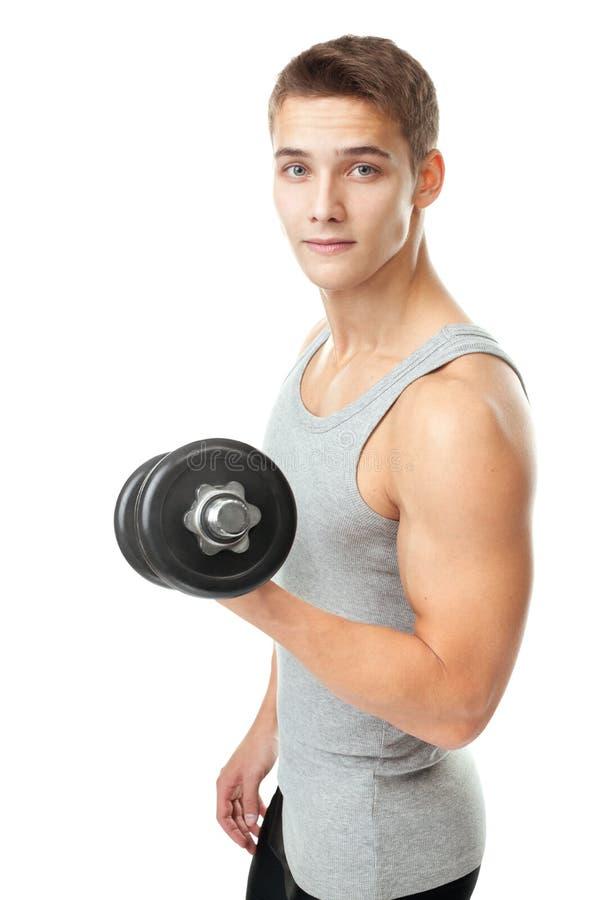 Bodybuilder des jungen Mannes, der mit Dummköpfen trainiert stockfotos