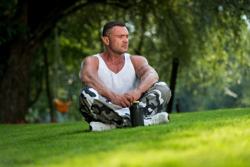 Bodybuilder die in Aard rusten stock foto's
