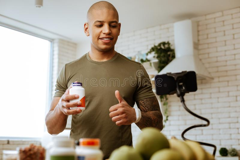 Bodybuilder die duim tonen terwijl het filmen van video over vitaminen stock foto