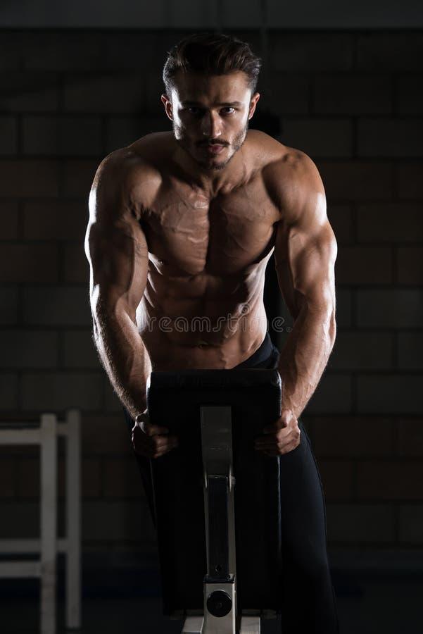 Bodybuilder die Duw UPS op Bank uitoefenen stock afbeeldingen