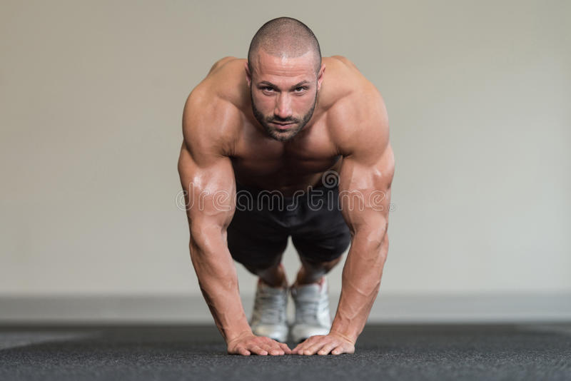 Bodybuilder die Duw UPS op Vloer uitoefenen stock foto's