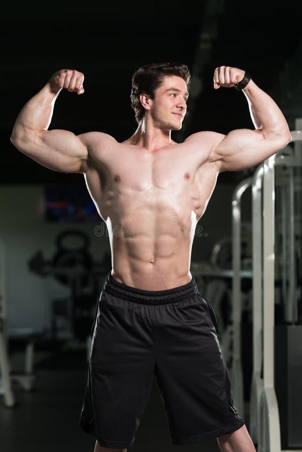 Bodybuilder die Front Double Biceps Pose In-Gymnastiek uitvoeren stock foto