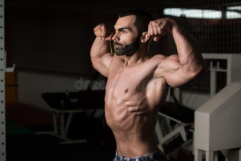 Bodybuilder die Front Double Biceps Pose uitvoeren royalty-vrije stock afbeeldingen