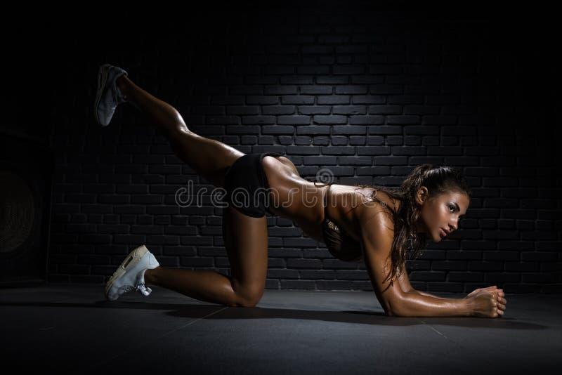 Bodybuilder die oefeningen voor billen doen stock afbeelding