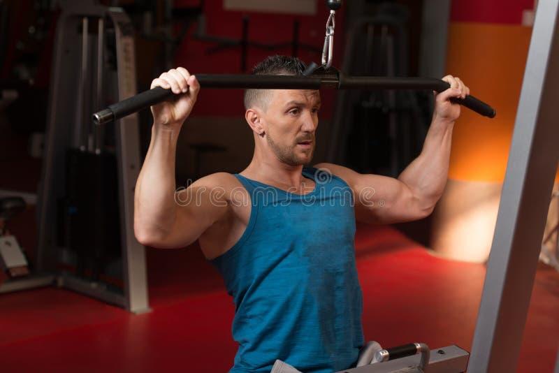 Bodybuilder die terug in Gymnastiek uitoefenen stock foto