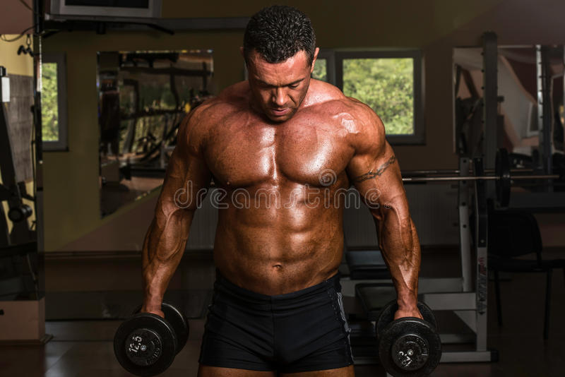 Bodybuilder doing heavy weight exercise for biceps with dumbbell royalty free stock photography