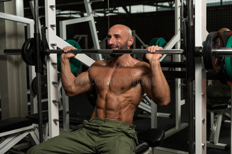 Bodybuilder Doing Heavy Weight Exercise For Shoulder. Mature Man Doing Shoulder Exercises In The Gym stock images