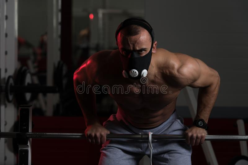 Athlete Exercising Push-Ups On Barbell In Elevation Mask. Bodybuilder Doing Push Ups On Barbell As Part Of Bodybuilding Training In Elevation Mask royalty free stock photography