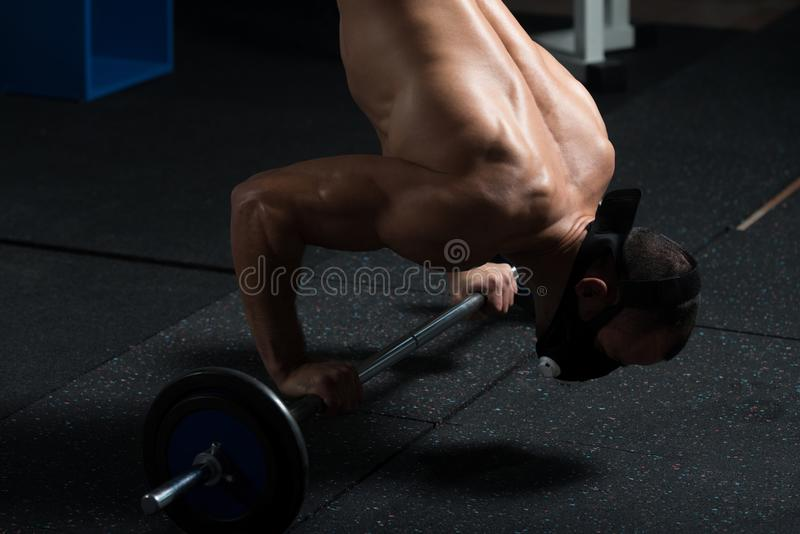 Athlete Exercising Push-Ups On Barbell In Elevation Mask. Bodybuilder Doing Push Ups On Barbell As Part Of Bodybuilding Training In Elevation Mask stock photos
