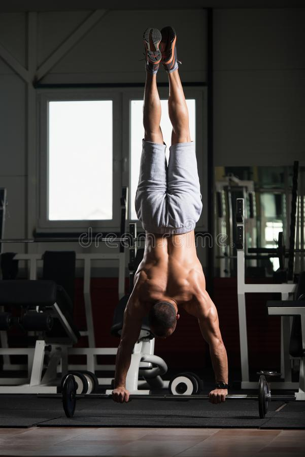Athlete Exercising Push-Ups On Barbell In Elevation Mask. Bodybuilder Doing Push Ups On Barbell As Part Of Bodybuilding Training In Elevation Mask royalty free stock images