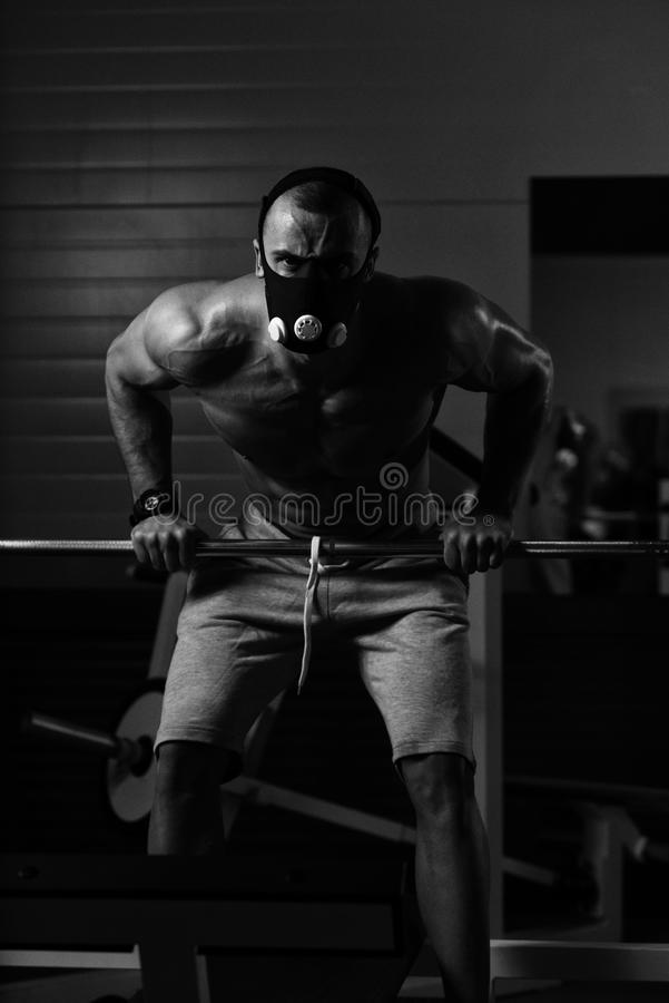 Bodybuilder Exercising Push-Ups On Barbell In Elevation Mask. Bodybuilder Doing Push Ups On Barbell As Part Of Bodybuilding Training In Elevation Mask royalty free stock images