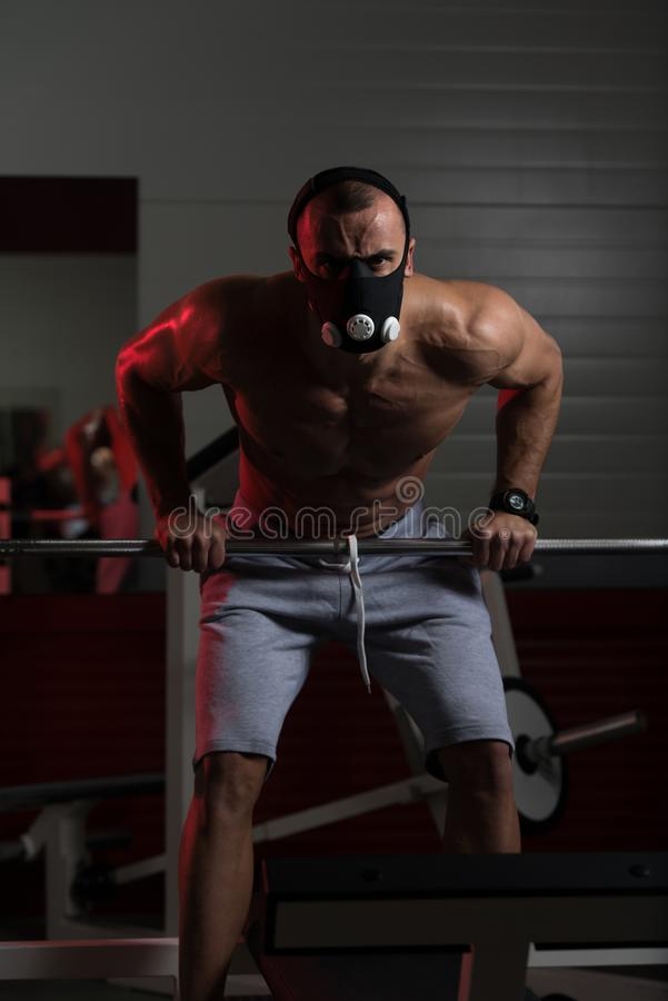 Bodybuilder Exercising Push-Ups On Barbell In Elevation Mask. Bodybuilder Doing Push Ups On Barbell As Part Of Bodybuilding Training In Elevation Mask stock image