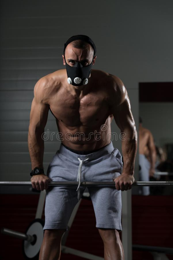 Man Exercising Push-Ups On Barbell In Elevation Mask. Bodybuilder Doing Push Ups On Barbell As Part Of Bodybuilding Training In Elevation Mask royalty free stock image