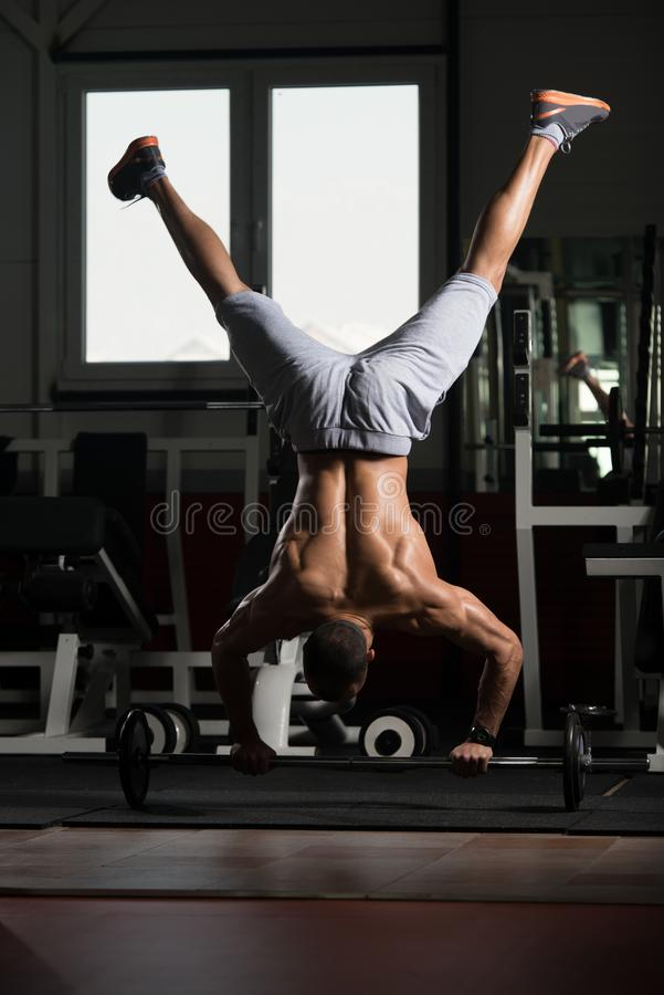 Man Exercising Push-Ups On Barbell In Elevation Mask. Bodybuilder Doing Push Ups On Barbell As Part Of Bodybuilding Training In Elevation Mask royalty free stock photo