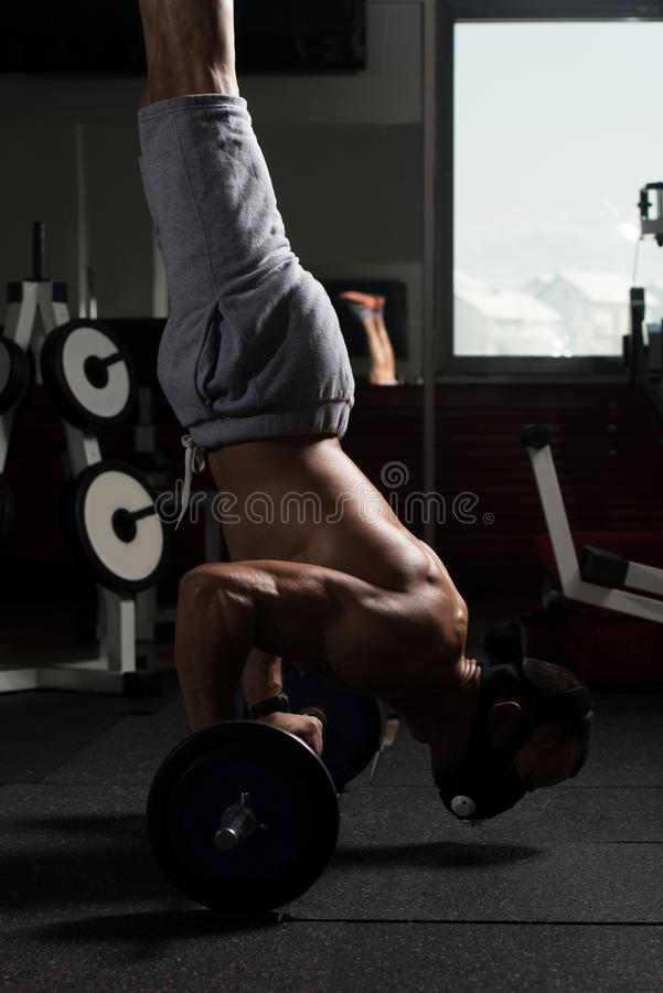 Man Exercising Push-Ups On Barbell In Elevation Mask. Bodybuilder Doing Push Ups On Barbell As Part Of Bodybuilding Training In Elevation Mask stock photo