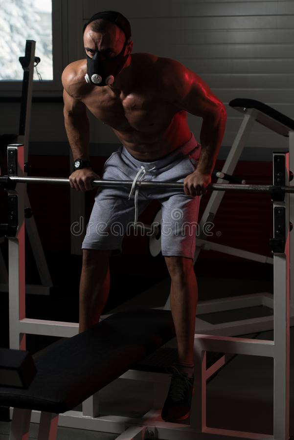 Man Exercising Push-Ups On Barbell In Elevation Mask. Bodybuilder Doing Push Ups On Barbell As Part Of Bodybuilding Training In Elevation Mask royalty free stock photos