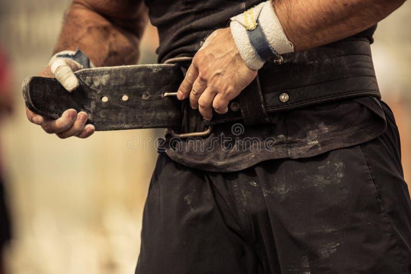 Bodybuilder enserrant sur sa ceinture de bodybuilding image stock