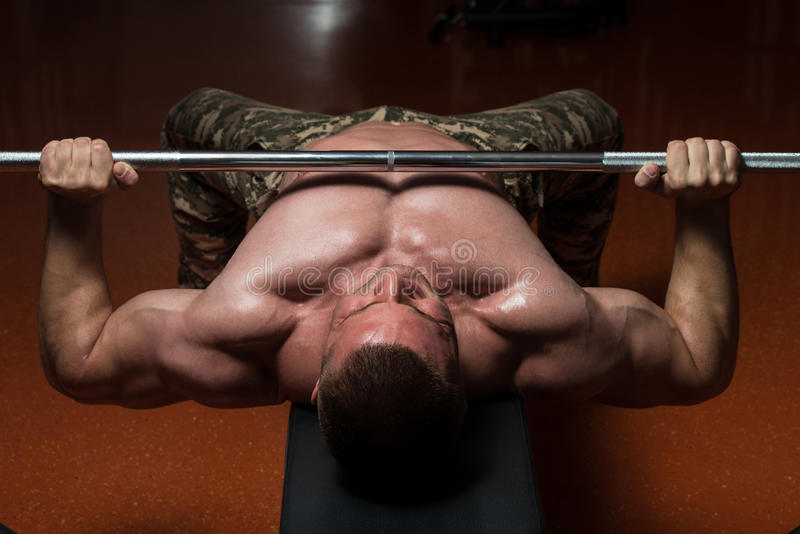 Bodybuilder exerçant le coffre avec le Barbell photo stock