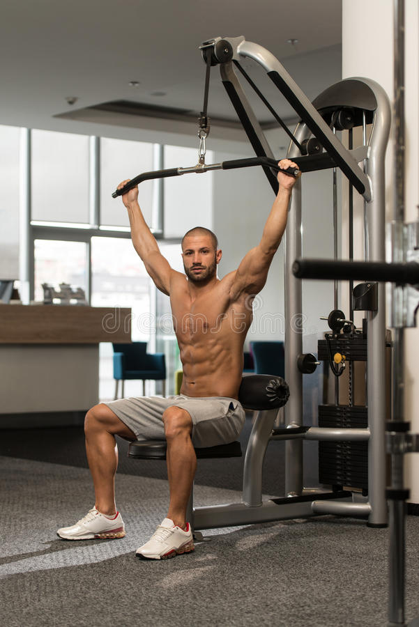 Bodybuilder Exercising Back on Machine. Young Bodybuilder Doing Heavy Weight Exercise For Back On Machine royalty free stock photography