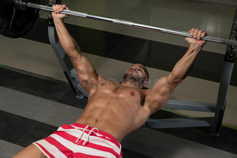 Bodybuilder Exercising Chest With Barbell stock photos