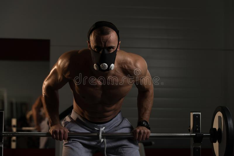 Bodybuilder Exercising Push-Ups On Barbell In Elevation Mask. Bodybuilder Doing Push Ups On Barbell As Part Of Bodybuilding Training In Elevation Mask stock photo