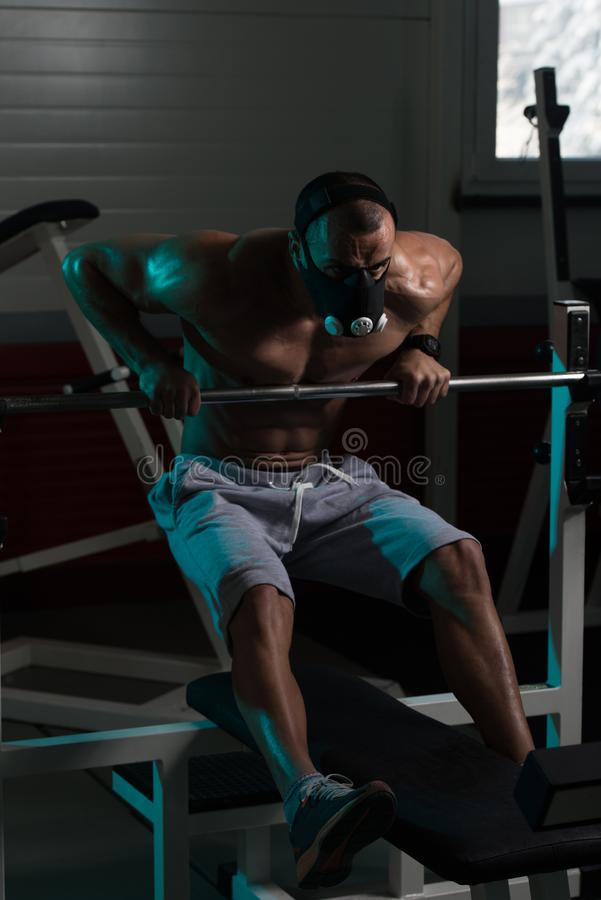Bodybuilder Exercising Push-Ups On Barbell In Elevation Mask. Bodybuilder Doing Push Ups On Barbell As Part Of Bodybuilding Training In Elevation Mask stock photos