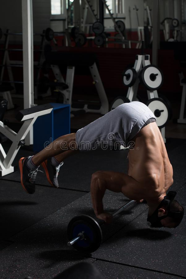 Bodybuilder Exercising Push-Ups On Barbell In Elevation Mask. Bodybuilder Doing Push Ups On Barbell As Part Of Bodybuilding Training In Elevation Mask royalty free stock photos