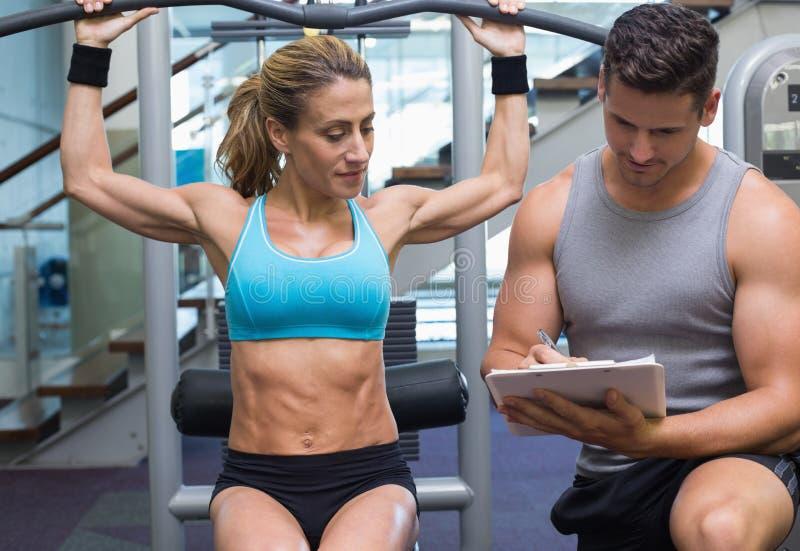Bodybuilder féminin à l'aide de la machine de poids pour des bras avec l'entraîneur prenant des notes photo stock