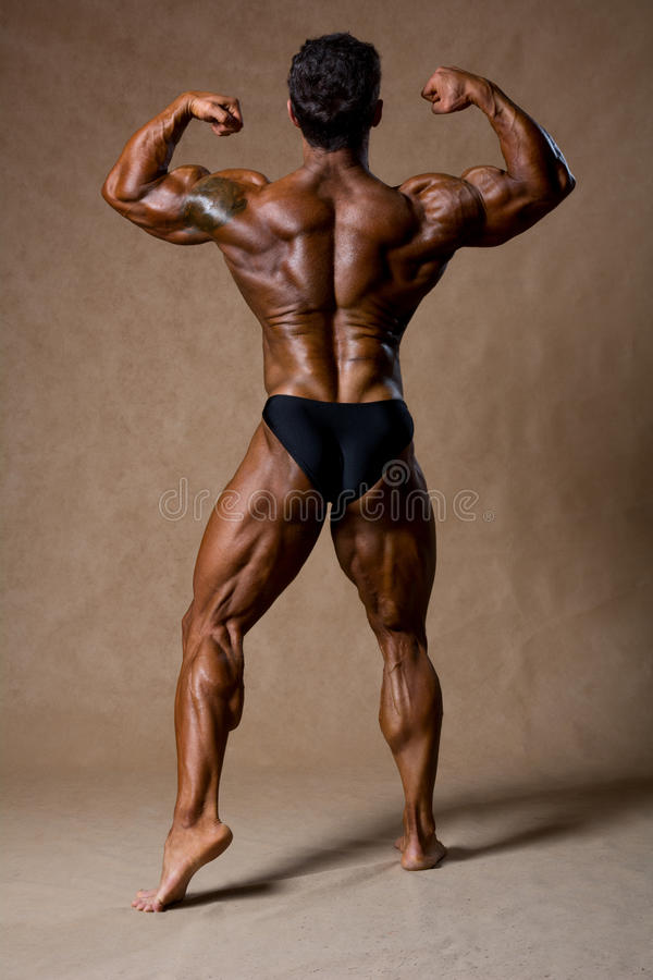 Bodybuilder flexing his muscles in studio. royalty free stock photography