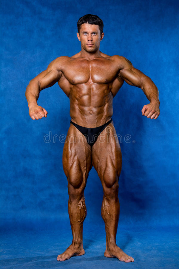 Bodybuilder flexing his muscles in studio. Mandatory poses bodybuilders. On a blue background royalty free stock photography