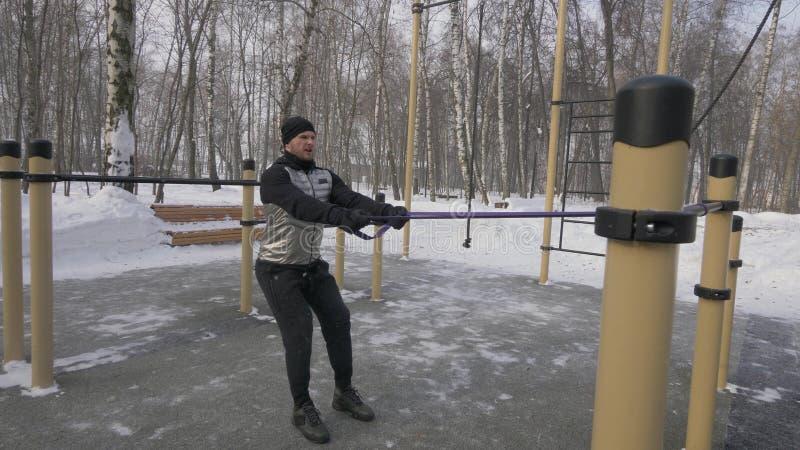 Bodybuilder formant l'exercice anaérobie avec l'extenseur sur la formation extérieure d'hiver photos stock