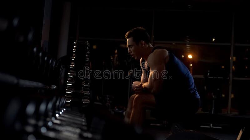 Bodybuilder fort se reposant après séance d'entraînement intensive avec des haltères au gymnase images libres de droits