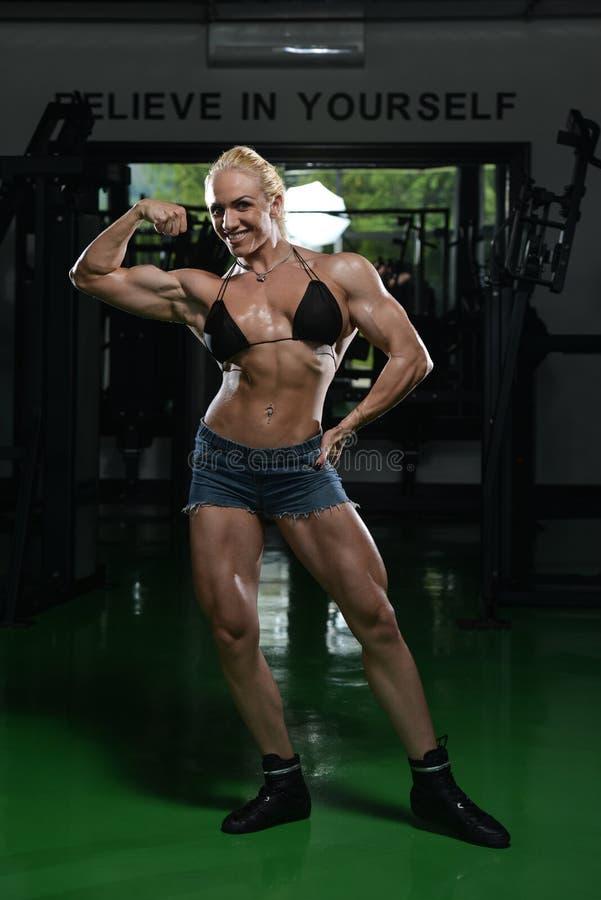 Bodybuilder Front Biceps Pose de exécution de femme images libres de droits