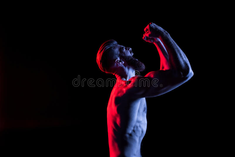 Bodybuilder gesturing and yelling isolated on black with dramatic lighting. Handsome bodybuilder gesturing and yelling isolated on black with dramatic lighting stock photo