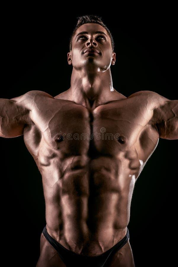 Bodybuilder glory. Close-up shot of a handsome muscular bodybuilder posing over black background royalty free stock image