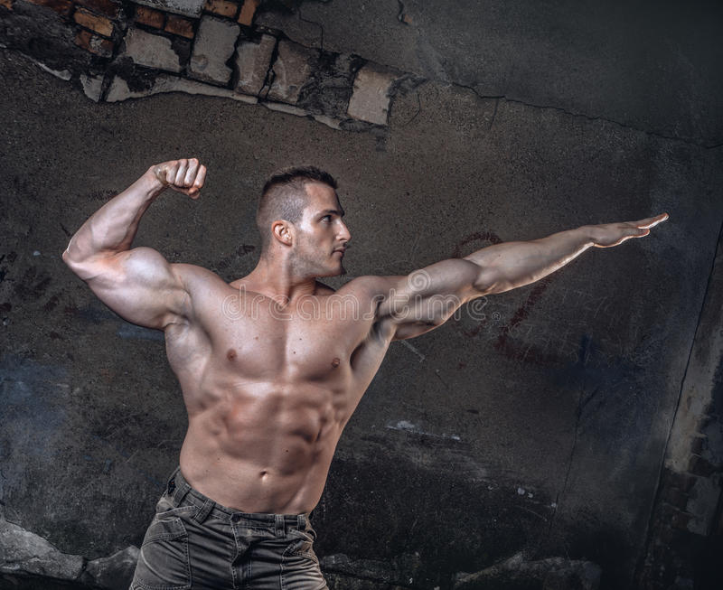 Bodybuilder on grunge wall stock images