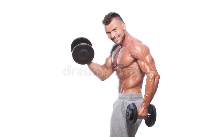Bodybuilder guy doing exercises with dumbbells royalty free stock photos