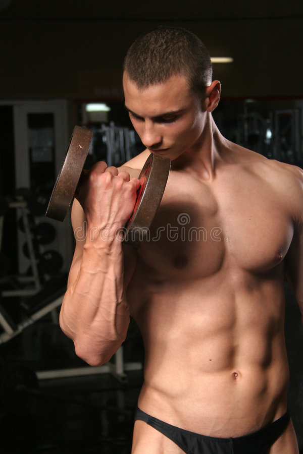 Bodybuilder in the gym. Training shot of young muscular man in the gym stock photography